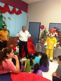 Fire Department staff and Sparky the Fire Dog speak with children