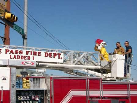 Sparky the Fire Dog and firefighters ride on a truck during a parade